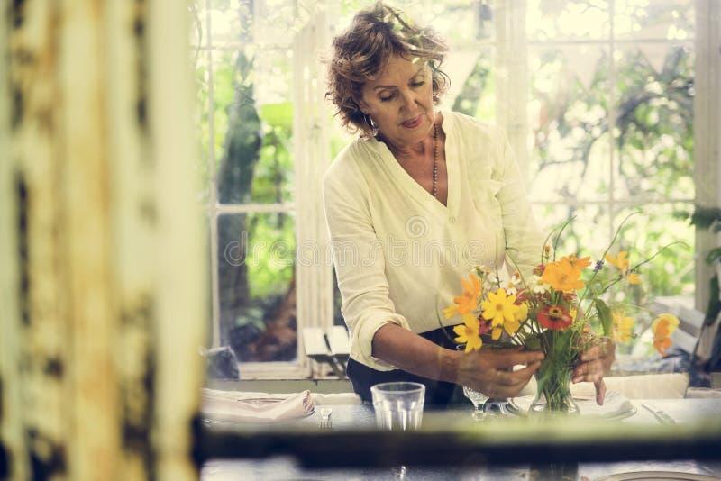 Vrouw die bloemen in het huis schikken royalty-vrije stock foto's