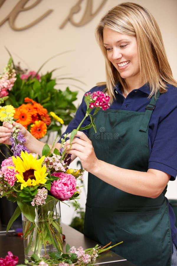 Vrouw die in bloemist werkt stock afbeelding