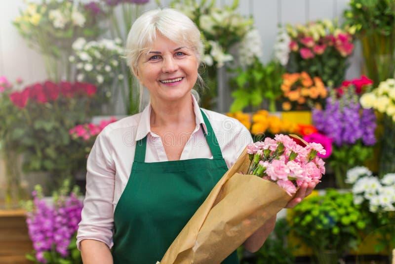 Vrouw die in bloemistwinkel werken stock foto