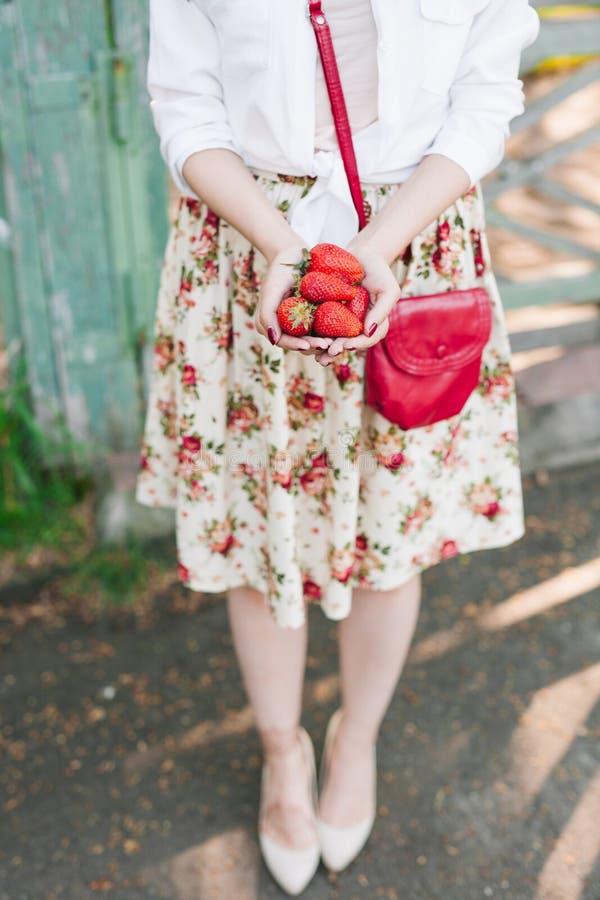 Vrouw die in bloemkleding een bos van aardbeien houden stock foto