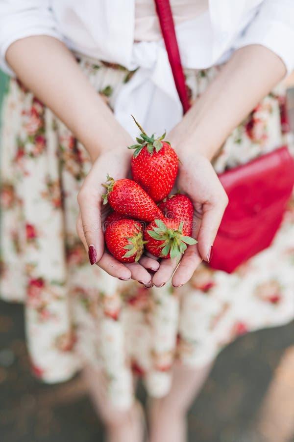Vrouw die in bloemkleding een bos van aardbeien houden stock afbeeldingen