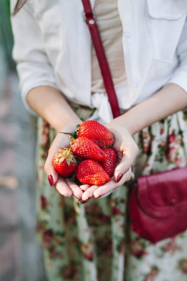 Vrouw die in bloemkleding een bos van aardbeien houden stock foto's