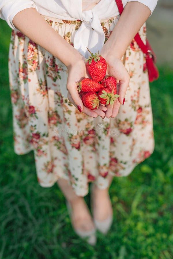 Vrouw die in bloemkleding een bos van aardbeien houden royalty-vrije stock foto