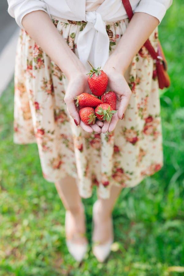 Vrouw die in bloemkleding een bos van aardbeien houden royalty-vrije stock foto's