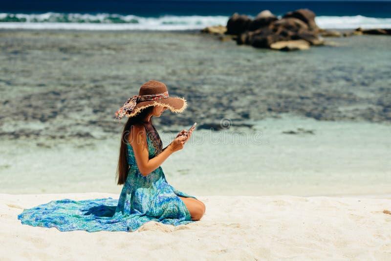 Vrouw die blogger smartphone op strand gebruiken stock afbeelding
