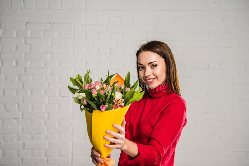 Vrouw die boeket van bloemen tonen stock foto's