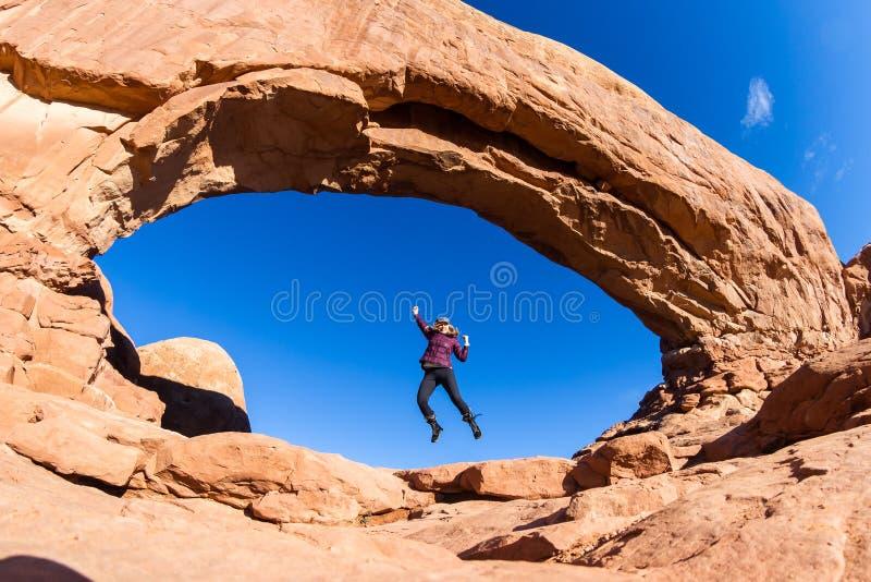 Vrouw die in Bogen springen stock foto's