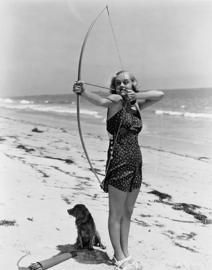 Vrouw die boog en pijl op strand schieten (Alle afgeschilderde personen leven niet langer en geen landgoed bestaat Leveranciersga stock afbeeldingen