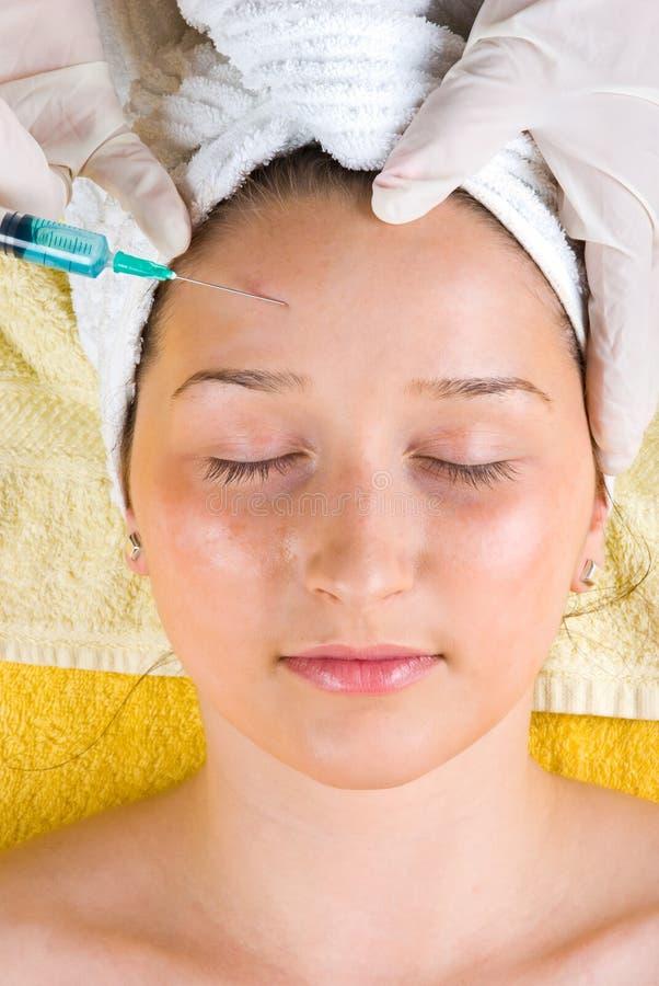 Vrouw die botox injectie krijgt aan voorhoofd stock fotografie