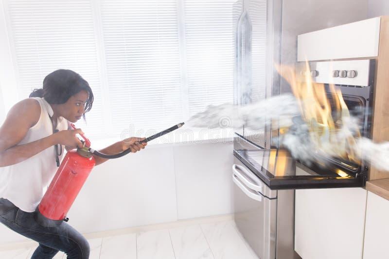 Vrouw die Brandblusapparaat gebruiken om Brand tegen te houden volgend uit Oven royalty-vrije stock fotografie