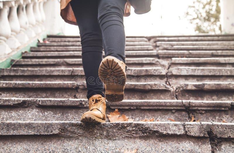 Vrouw die Bruine Leerlaarzen dragen Het lopen onderaan de treden stock foto