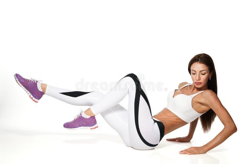 Vrouw die buikdieduwups houding uitoefenen op wit wordt geïsoleerd stock afbeeldingen