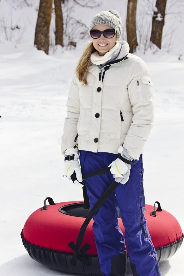 Vrouw die buizenstelsel van de pret het gaande sneeuw op een de winterdag hebben stock afbeelding