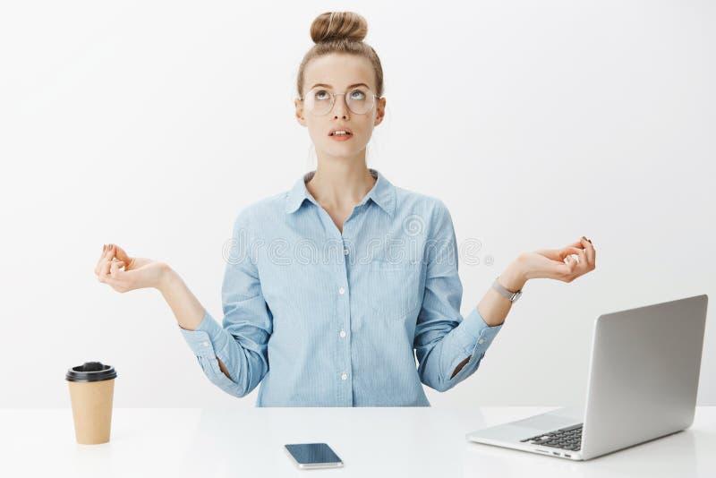 Vrouw die in bureauzitting dichtbij lijst mediteren die onderbreking van het schrijven van artikel in laptop hebben, drinkend kof royalty-vrije stock fotografie