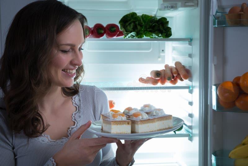 Vrouw die Cake eten dichtbij de Koelkast royalty-vrije stock fotografie