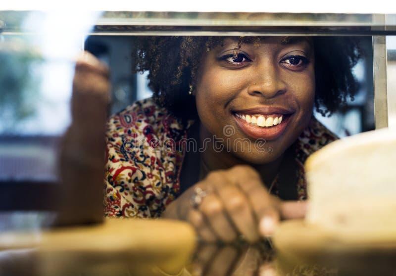 Vrouw die cake krijgen uit de vertoningskoelkast stock fotografie