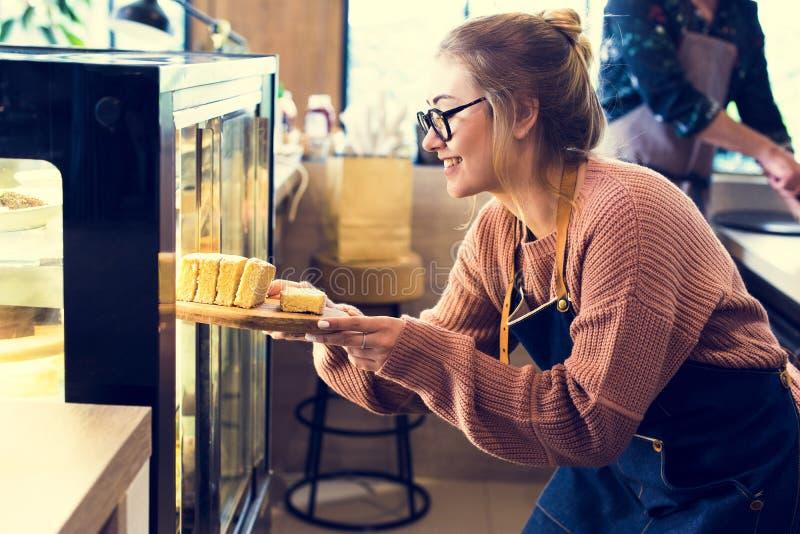 Vrouw die cake krijgen uit de vertoningskoelkast stock afbeeldingen