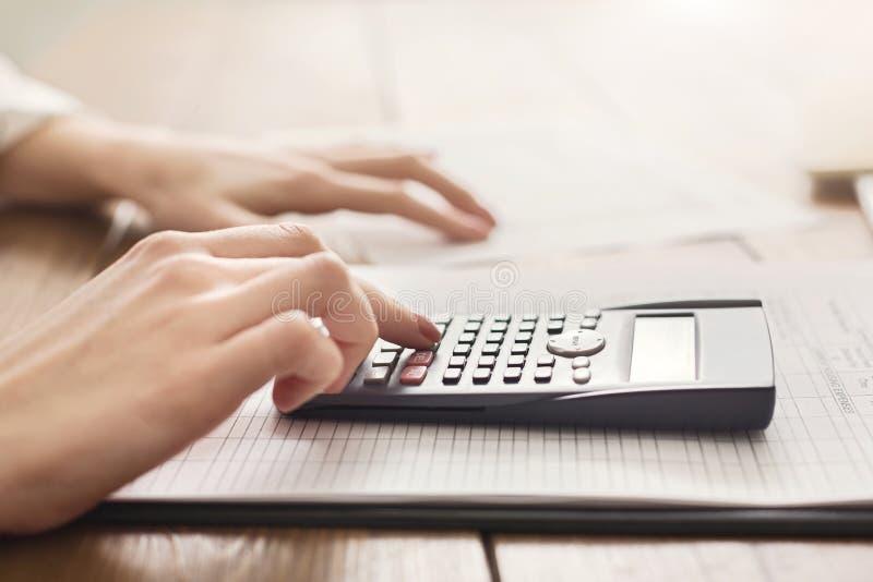 Vrouw die calculator met thuis het controleren van financiën gebruiken royalty-vrije stock foto's