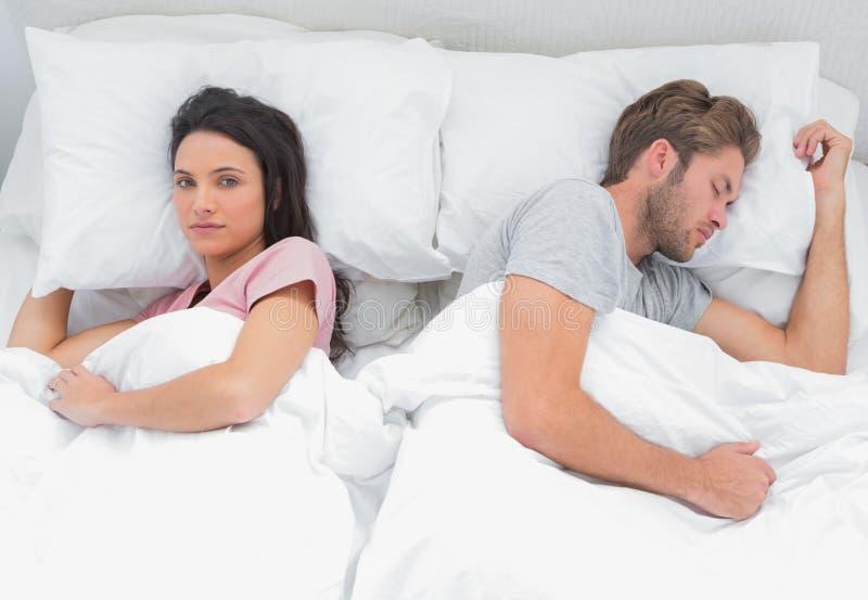 Vrouw die camera bekijken terwijl haar echtgenoot slaapt stock foto's