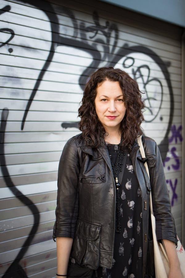 Vrouw die camera voor graffitimuur onder ogen zien stock foto's