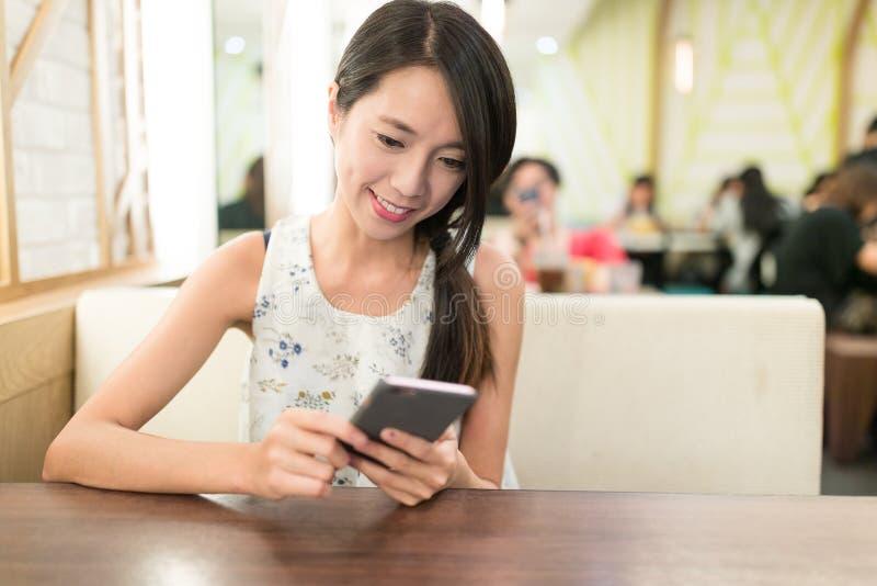 Vrouw die cellphone gebruiken bij restaurant royalty-vrije stock afbeeldingen