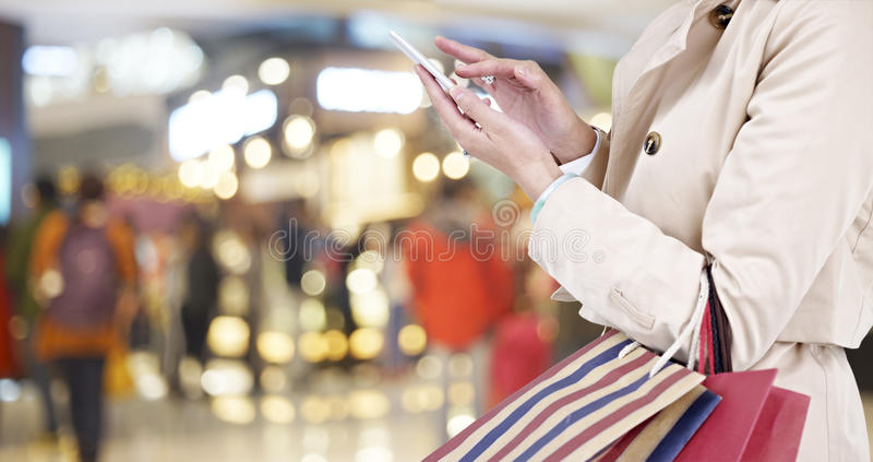 Vrouw die cellphone gebruiken terwijl het winkelen stock afbeelding
