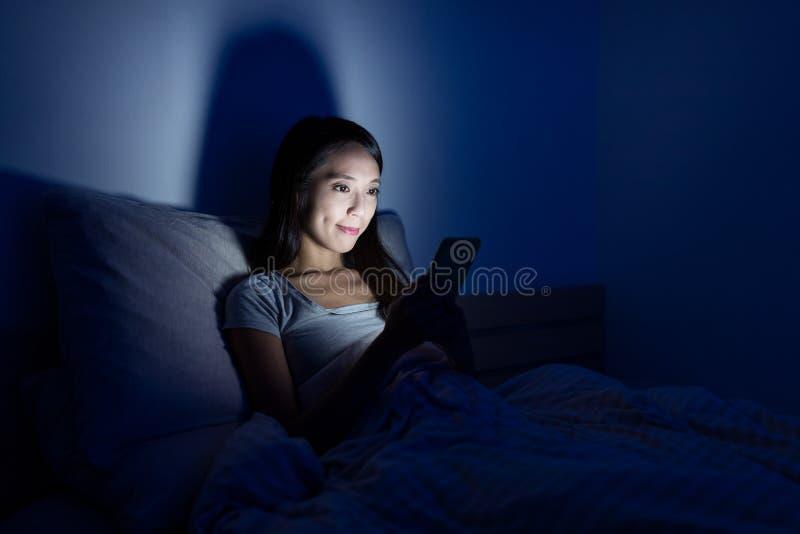 Vrouw die cellphone op bed gebruiken bij nacht royalty-vrije stock foto