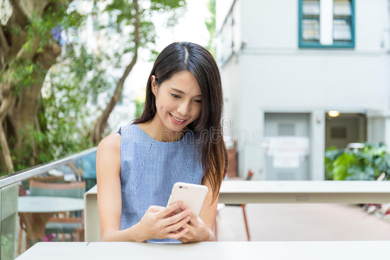 Vrouw die cellphone in openluchtkoffie gebruiken royalty-vrije stock foto's