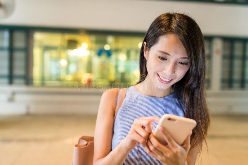 Vrouw die cellphone in winkelcomplex gebruiken royalty-vrije stock afbeeldingen