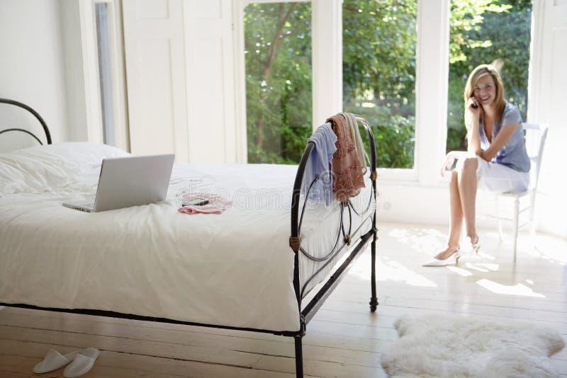 Vrouw die Celtelefoon met Laptop op Bed met behulp van stock fotografie