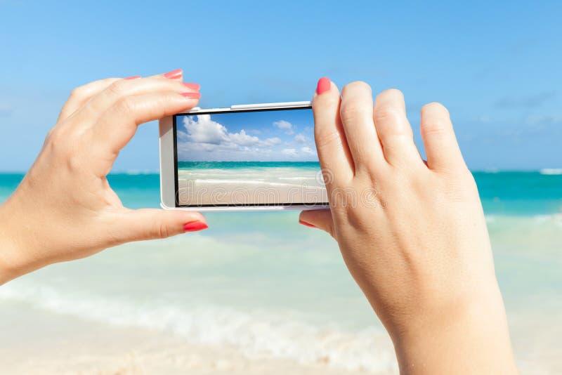 Vrouw die celtelefoon voor het nemen van overzeese landschapsfoto met behulp van royalty-vrije stock fotografie