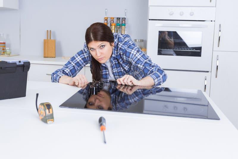 Vrouw die ceramische haardplaat passen in keukeneenheid royalty-vrije stock fotografie