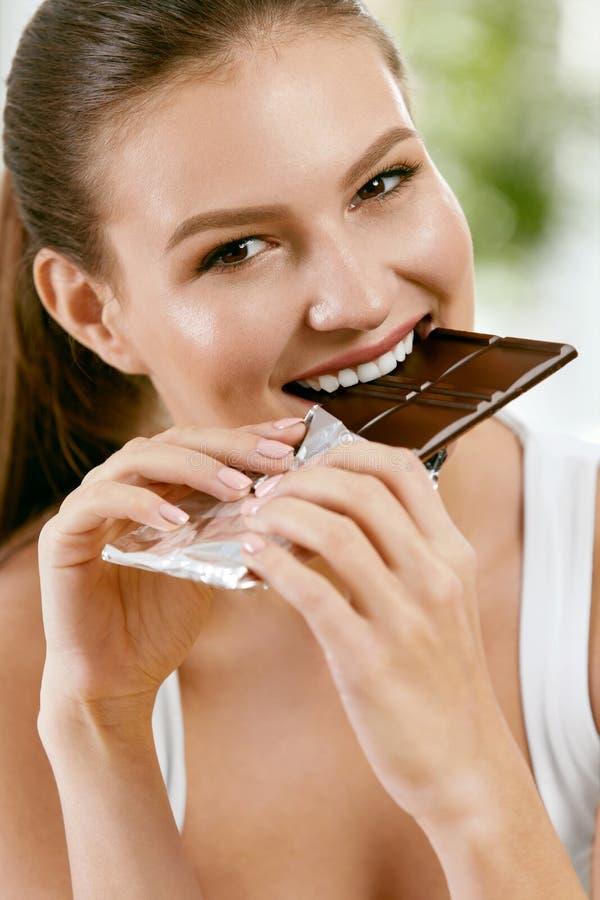 Vrouw die chocolade eet Mooi meisje met snoepjes royalty-vrije stock foto