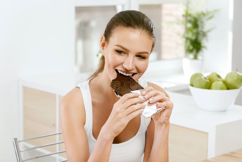 Vrouw die chocolade eet Mooi meisje met snoepjes royalty-vrije stock afbeelding