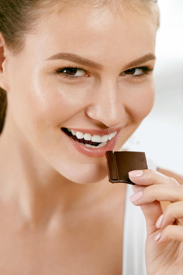 Vrouw die chocolade eet Mooi meisje met snoepjes stock afbeelding