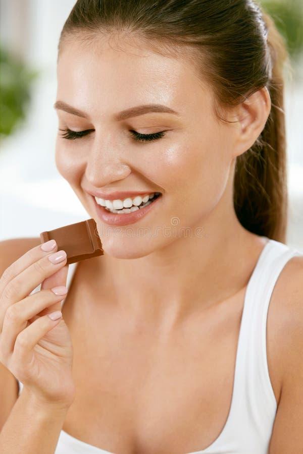 Vrouw die chocolade eet Mooi meisje met snoepjes stock foto