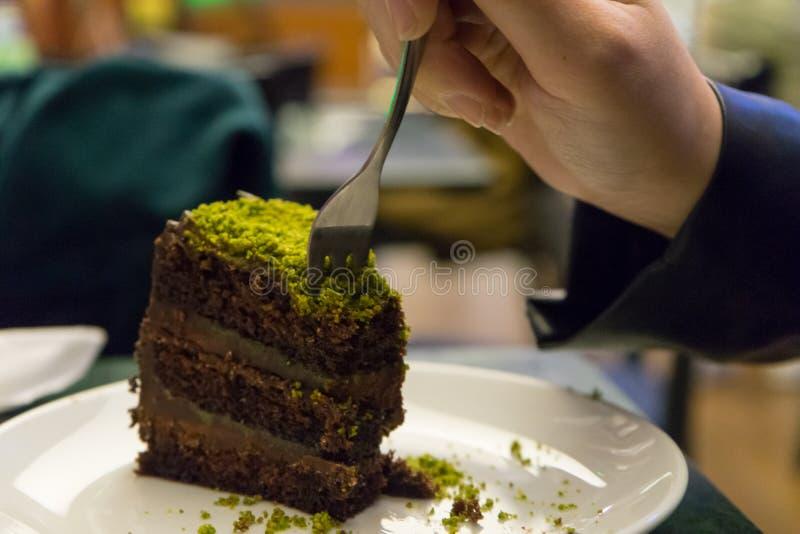 Vrouw die chocoladetaart eet met pistachio, een stuk op een stuk gekookt dessert in een restaurant Hand met Fork-smaak stock afbeeldingen