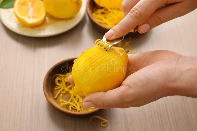 Vrouw die citroenschil met zester opstijgen royalty-vrije stock foto