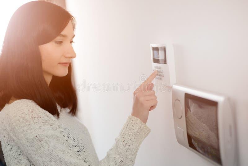 Vrouw die code inzake toetsenbord van het alarm van de huisveiligheid ingaan
