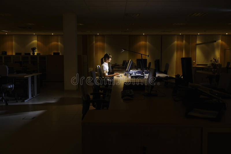 Vrouw die Computer in Donker Bureau met behulp van royalty-vrije stock afbeelding