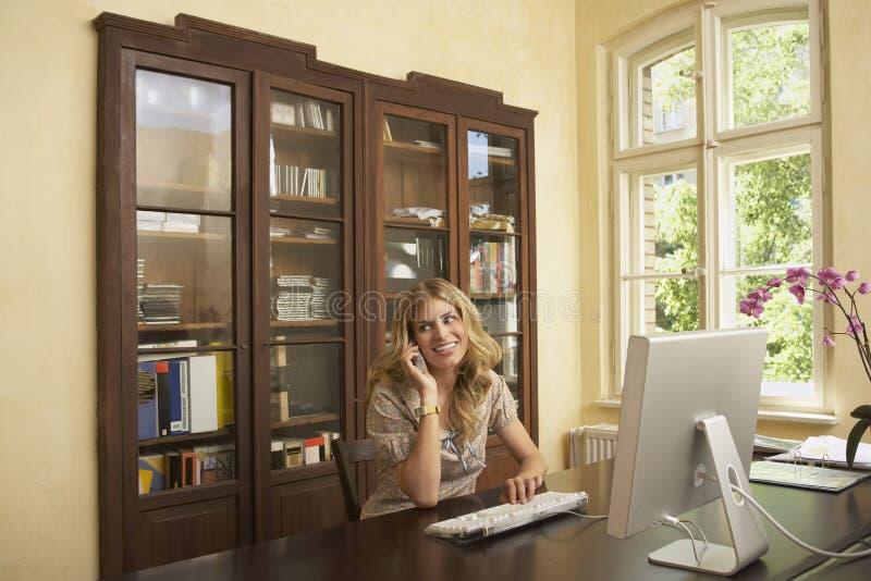 Vrouw die Computer en Cellphone in Studiezaal gebruiken stock afbeelding