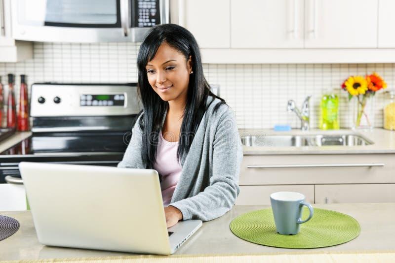 Vrouw die computer in keuken met behulp van royalty-vrije stock afbeelding