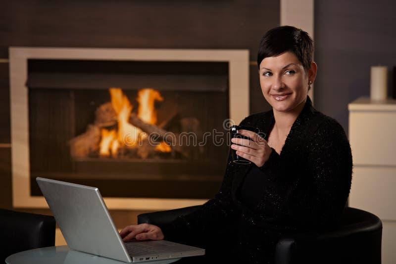 Vrouw die computer thuis met behulp van stock afbeelding