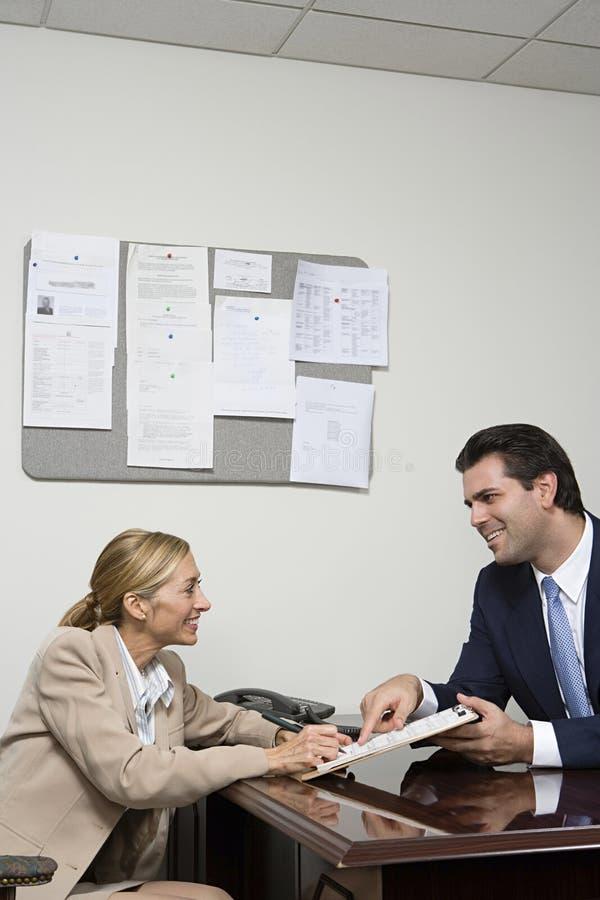 Vrouw die contract ondertekenen stock foto's
