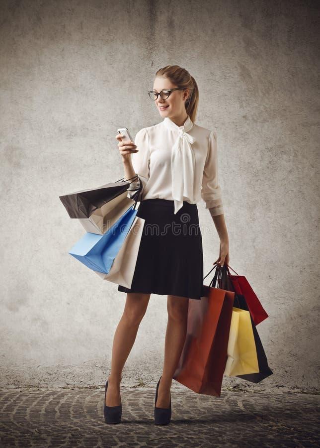 Vrouw die controlerend haar telefoon winkelen stock foto's