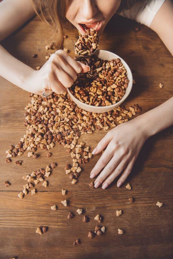 Vrouw die cornflakes in slordige ruimte na partij eten royalty-vrije stock fotografie