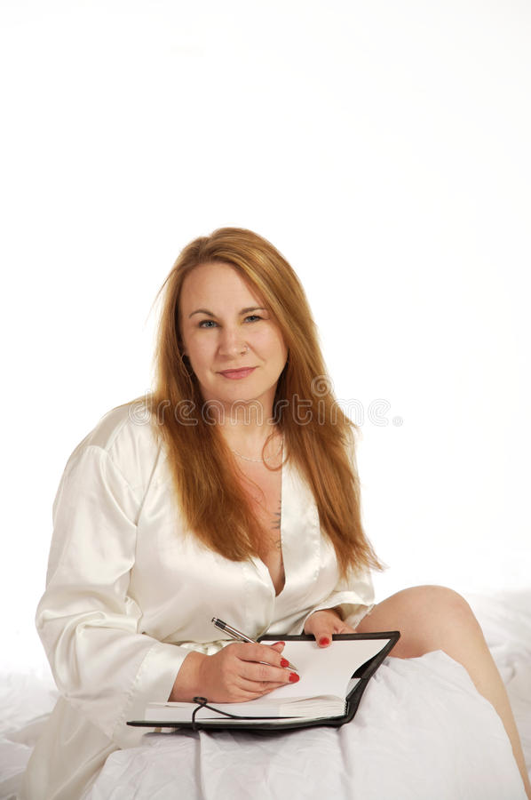 Vrouw die in dagboek schrijft stock afbeelding