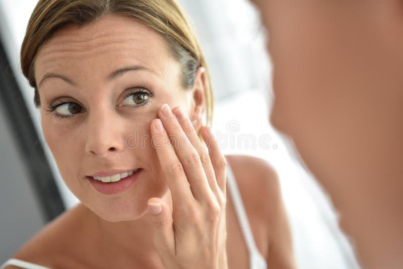 Vrouw die dagelijkse room op haar gezicht toepassen royalty-vrije stock foto's