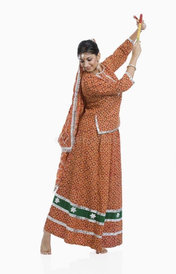 Vrouw die Dandiya-Raas op Navratri uitvoeren stock foto
