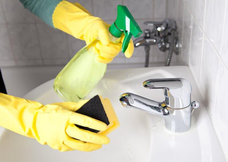 Vrouw die de badkamers schoonmaakt stock afbeeldingen